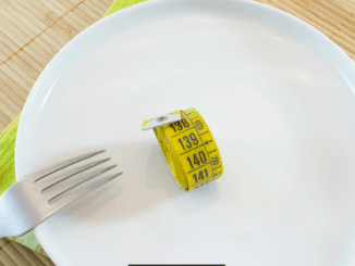 Image of a plate with a measuring tape and fork. Diet concept