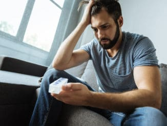 Depressed gloomy bearded man holding a pill organizer and looking at it while being ill