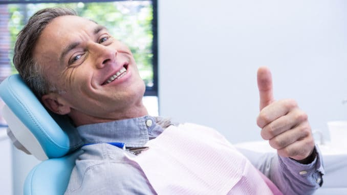Portrait of smiling man showing thumbs up while sitting on chair at dentist clinic