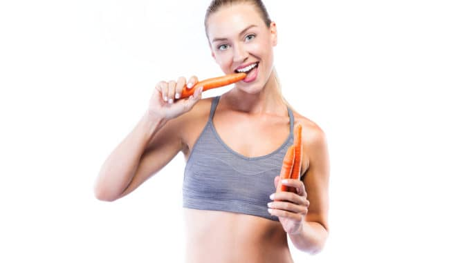 Portrait of beautiful young woman eating carrots over white background.