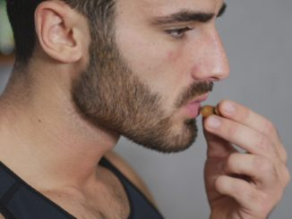 Young athletic man eating almonds in kitchen, choosing a healty lifestyle