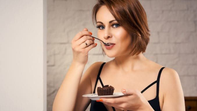 Attractive woman eating chocolate cake at home on couch
