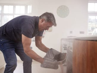 Middle aged man opening smoke filled oven in the kitchen