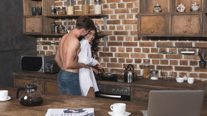 Young beautiful couple cooking breakfast together