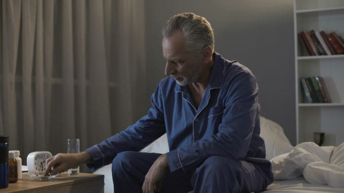 Sad aged person sitting on couch and taking painkillers, health problems, stock footage