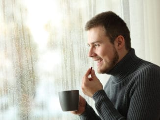 Side view portrait of a happy man taking a pill looking through a window in a rayny day of winter at home