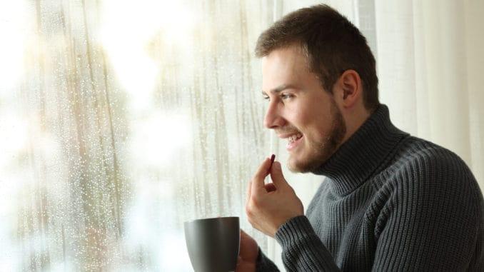 man taking a pill looking through a window