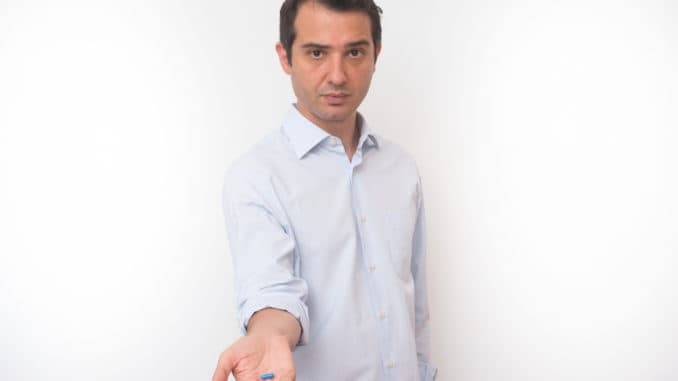 Man showing a bunch of medicine pills in his hand