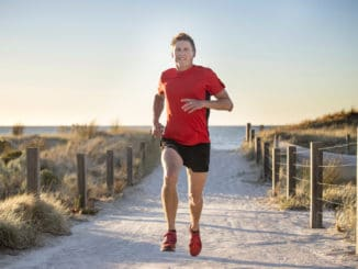 Young attractive and happy sport runner man with fit and strong healthy body training on off road track in Summer running workout under Summer sun in health care and competition concept