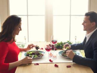 Young men and women having romantic dinner in the restaurant eating salad enjoying food