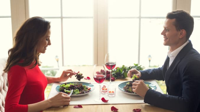 Young men and women having romantic dinner in the restaurant eating salad enjoying food