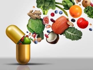 Vitamins supplements as a capsule with fruit vegetables nuts and beans inside a nutrient pill as a natural medicine health treatment