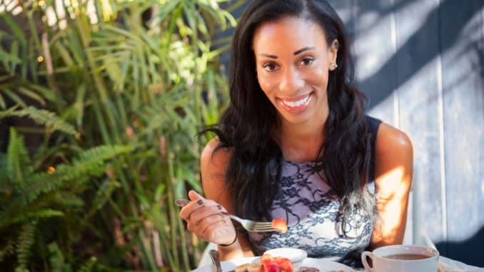 Beautiful dark skinned girl with a broad charming smile having breakfast with french toasts, fruits and berries.