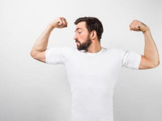 A handsome confident young man standing and showing big muscles on his hands. He is looking at one of them and very proud of them. He is wearing a white t-shirt, on white background