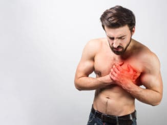 Picture of young and good-looking having a heart ache in his chest.