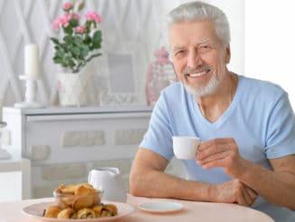 Portrait of smiling senior man drinking tea at home