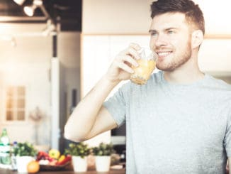 Handsome young man drinking orange juice in kitchen in the morning