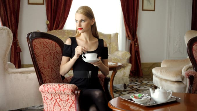 Attractive woman having tea time in a luxury hotel room