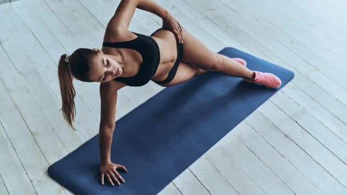 woman in sport clothing keeping side plank pose while exercising in the gym