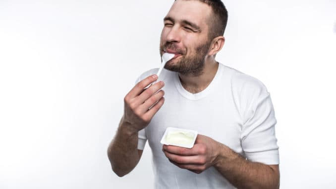 Young and strong man is eating yogurt.