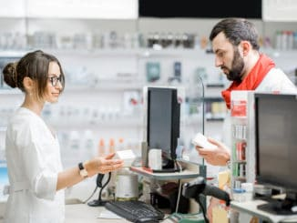 Man buying medication standing with pharmacist at the counter of the pharmacy store
