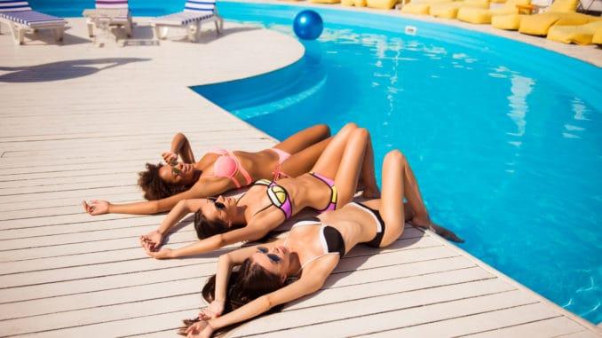 Happy three girls sun bathing near the pool.