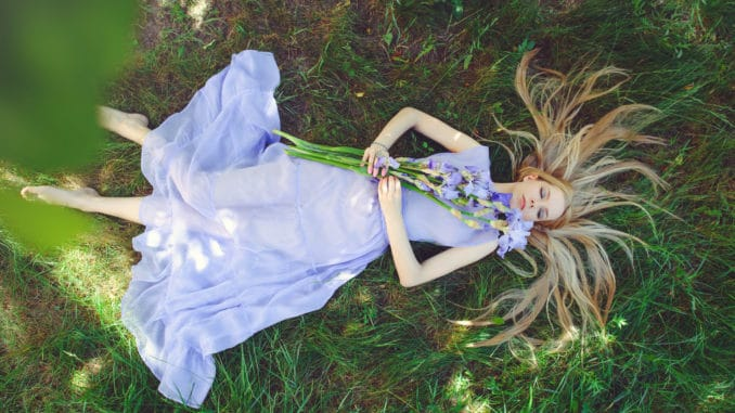 Attractive young girl with blonde hair and natural make-up smelling blue purple iris flowers lying on grass outdoors, tenderness and softness on nature background.