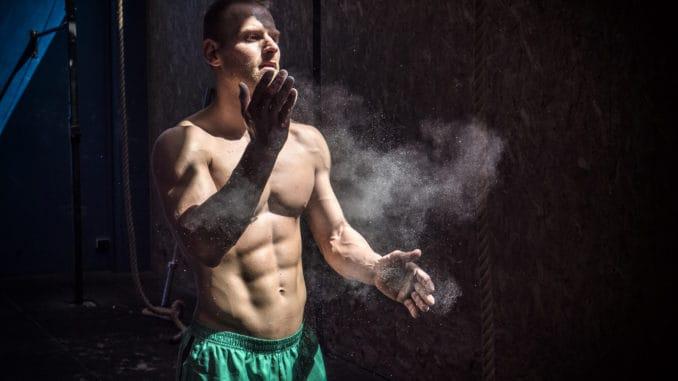 Shirtless man using chalk or magnesium powder in gym