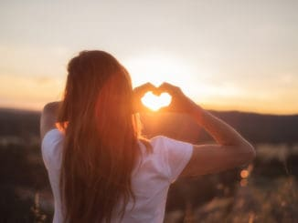 Love sign. Woman making heart with her hands at sunset .