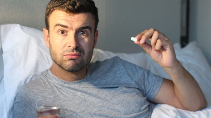 Man taking a pill in bed.