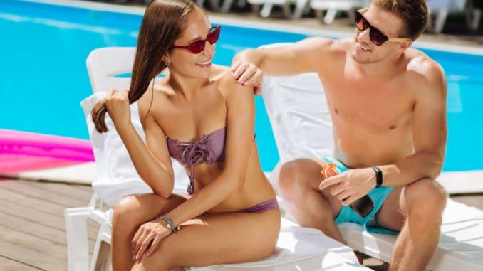 Putting cream. Caring boyfriend wearing dark sunglasses putting sun protection cream on skin of girlfriend