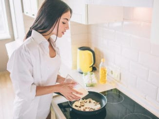 Beautiful young woman is cooking breakfast. She is pouring mixed eggs and milk into frying pan with mushrooms. Girl is cooking breakfast.
