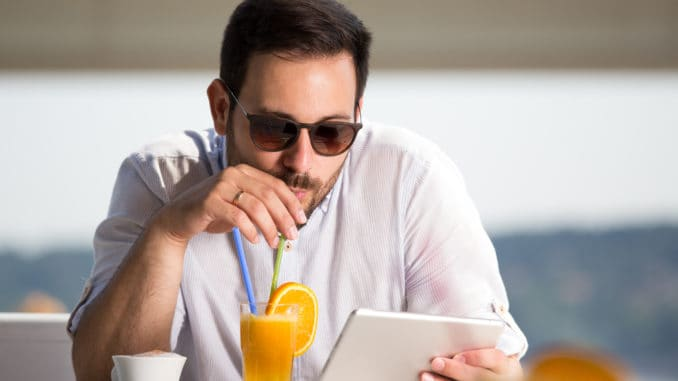 Handsome man with sunglasses drinking orange juice