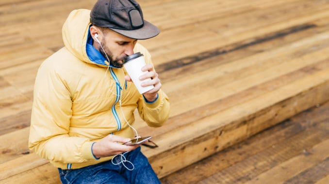 drinking delicious coffee and listening to music with earphones holding mobile phone