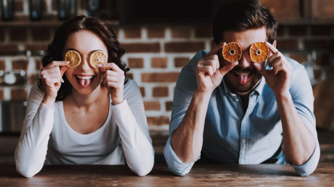 Beautiful Young Couple Having Fun in Kitchen. Handsome Smiling Woman and Man Having Fun with Colourful Oranges in Loft Kitchen. Family Preparing Dinner.