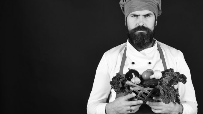 Man with beard on black background, copy space. Cook with serious face in burgundy uniform holds vegetables in wicker bowl. Chef holds lettuce, tomato, pepper and mushrooms. Vegetarian diet concept.