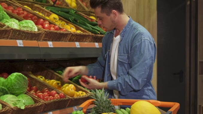 Blond caucasian guy buying fruits and vegetables at the hypermarket.