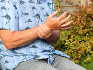 Elderly or senior man holding his wrist because of pains. Arthritis in his joints.