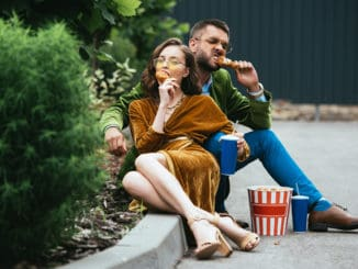 fashionable couple in velvet clothing eating fried chicken legs on street