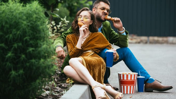 fashionable couple in velvet clothing eating fried chicken legs on street