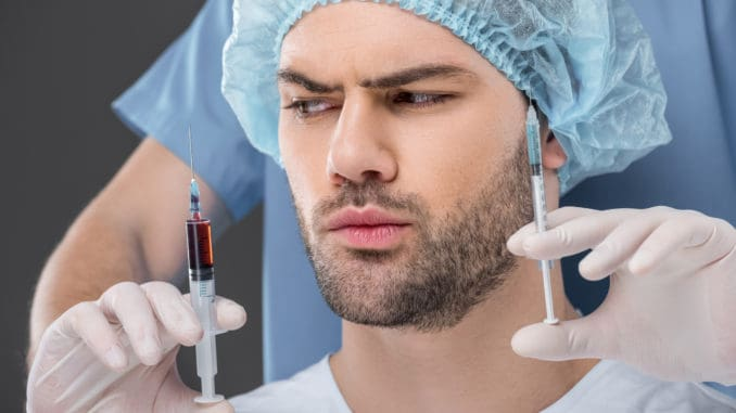 handsome man in medical cap choosing beauty injections isolated on grey
