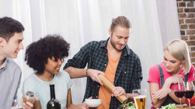 man adding spice to food with pepper grinder