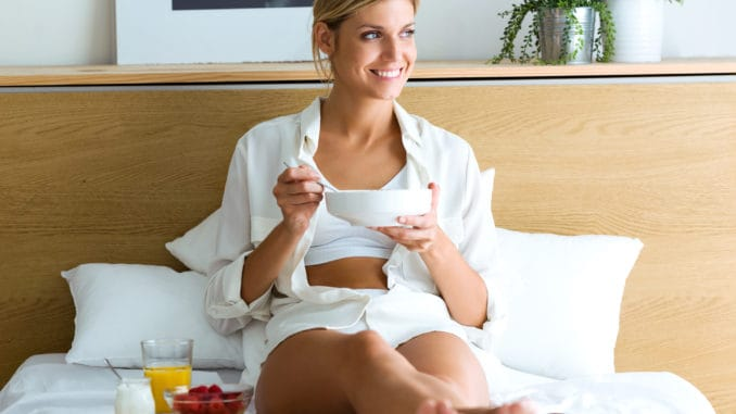 Shot of beautiful young woman having breakfast and looking outside while lying in the bed.