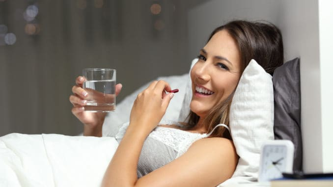Happy woman taking a pill holding a glass of water in the night looking at you