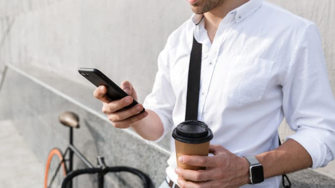 Photo of businesslike man 30s wearing sunglasses drinking takeaway coffee and using mobile phone while standing with bicycle along wall outdoor