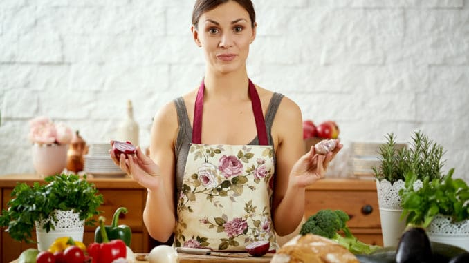 Beautiful young woman, brunette holds onions and garlic in the kitchen at a table full of organic vegetables