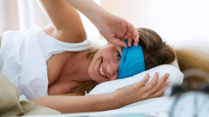 Portrait of pretty young woman pulling up sleeping mask
