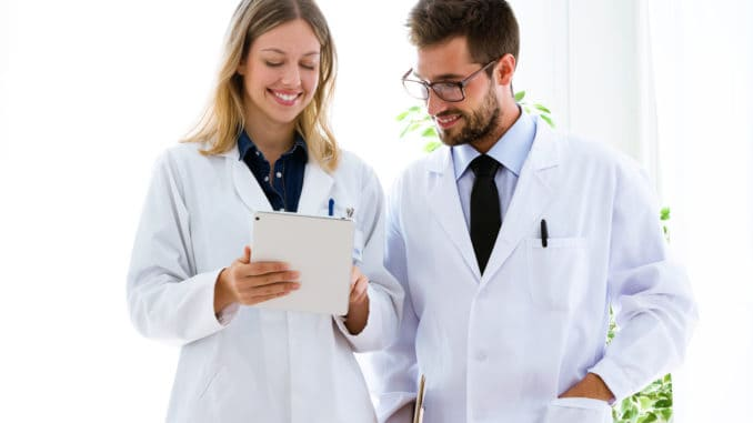 Shot of smiling young doctors looking medical reports in digital tablet in medical office