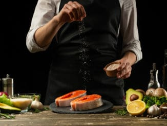 The chef prepares fresh salmon fish, smorgu trout, sprinkling salt with the ingredients.