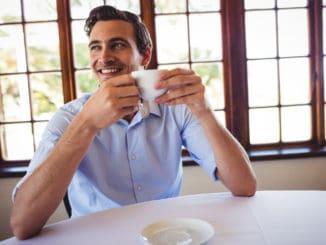 Smiling man having coffee in restaurant